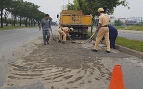 執勤交警同民眾用鏟子和掃把積極清理路面的泥土。