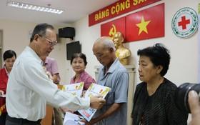 穗城會館理事長盧耀南向貧困同胞贈送醫保卡。