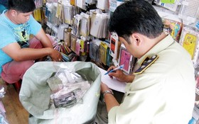 市場管理力量正檢查某電話配件專賣店的貨品。