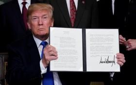 美國總統特朗普舉起剛簽署的總統備忘錄。(圖源:互聯網)