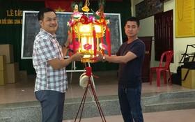"""陳昶霖(左)與陳良(右)喜迎""""蓮花寶燈""""。"""