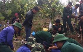 337國防經濟團所屬烈士骸骨搜集隊在挖掘烈士骸骨。(圖源:孟河)