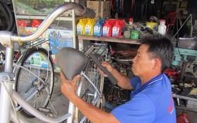 陳文富忙著翻新舊自行車。