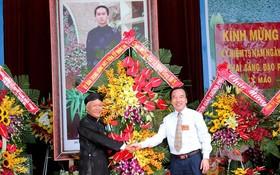 吳策實同志(右)代表越南祖國陣線中央委員會向和好佛教教會中央理事長贈送鮮花祝賀。(圖源:國忠)