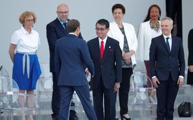 法國總統馬克龍與前來出席國慶閱兵儀式的日本外務大臣河野太郎(前排中)握手。(圖源:路透社)