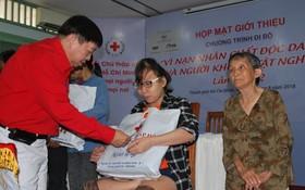 市紅十字會副主席張子諒向落葉劑受 害者和貧困殘疾人士贈送禮物。