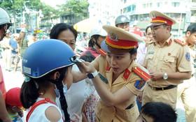 女交警向一名小學生贈送達標安全帽並指引正確的戴法。