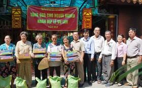 浸石天后宮理事長張敬和以及各理事向貧困同胞派發禮物。
