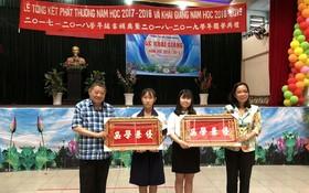 杭慰瑤董事長(左一)頒獎牌給品學兼優的學生。