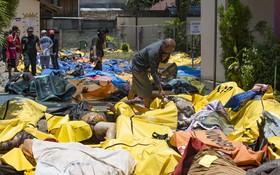 印尼蘇拉威西島9月28日發生7.5級淺層地震,觸發6米高海嘯,摧毀大量建築物,造成的死亡人數已上升到832人。圖為災民在醫院臨時停屍間找尋親友遺體。(圖源:AFP)