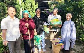 該廟慈善組組長鄒國榮(左一)與寶意禪寺 住持(右一)向少數民族貧困戶派發禮物。