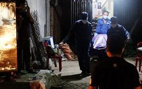 仵工將死者遺體搬出案發地點送上救護車。