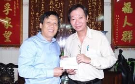 本報主編阮玉英(左)接受周華邦住持贊助善款。