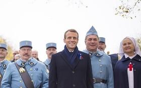 11月5日,法國莫朗格,法國總統馬克龍在當地的戰爭紀念館與身穿復古軍裝裝扮成一戰法國士兵的歷史愛好者合影。莫朗格戰爭紀念館當日舉行致敬儀式,慶祝第一次世界大戰結束一百週年。(圖源:互聯網)