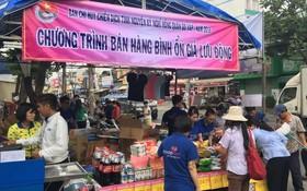 勞工在流動攤位選購平抑物價商品。