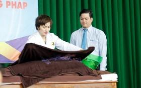 雪梅醫生在研討會上演示火療法治療方式。(圖源:黃蘭)