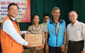 范興主任、詹木川組長和吳俊瑩會長(右起)向華人贈送禮物。