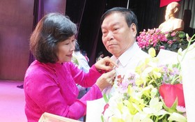 市委組織處副主任阮氏蘇珠向高齡黨員頒授黨齡紀念章。(圖源:蔡芳)