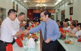 海南會館理事長吳清華向與會者派發新年紅包與大桔。