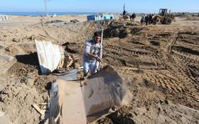3月9日,在加沙地帶南部城市汗尤尼斯,人們清理空襲現場。(圖源:新華社)