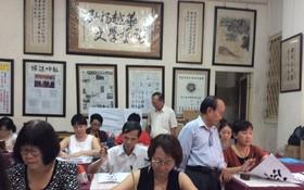 張路書畫家正在教學生練習書法。