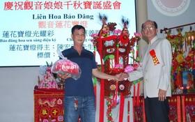 該廟理事長黃偉峰(右)向陳宏漢先生(左)轉交蓮花寶燈。