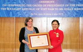 駐越南的戰爭遺產項目組織(WLP)創始人兼項目經理蘇珊‧瑪麗‧哈蒙德(左)從越南各友好組織聯合會(VUFO)主席阮芳娥手中接過獎狀。(圖源:越通社)