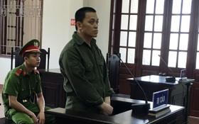 被告人何功慶站在被告席上答審判問案。(圖源:英豪)