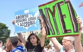 """抗議者舉著寫有""""保護安全、合法墮胎""""、""""我的身體我做主""""、""""墮胎是人權""""等標語的牌子,高喊""""解除禁令""""。(圖源:互聯網)"""