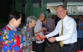 穗城會館理事長盧耀南向高齡鄉親贈送利是。