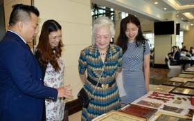 麒麟(左一)向華人同胞介紹其收藏的老堤岸事物。