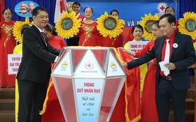 市彩票公司董事長阮國戰與陳長山主席設立捐款箱。