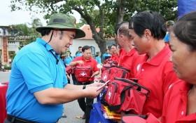 市勞動聯團常務委員副主席胡春霖(左)向崑崙島漁民贈送國旗和禮物。(圖源:勞動者報)