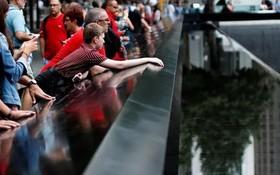 """在紐約""""九一一""""遺址紀念廣場,民眾在紀念碑旁悼念遇難者。(圖源:路透社)"""