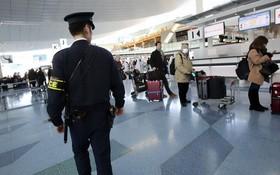 一名日本東京都警視廳反恐小組的警察在羽田機場國際到達航站樓內執勤。(圖源:AP)