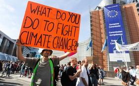 在比利時布魯塞爾民眾手持標語參加氣候變化遊行。(圖源:新華社)