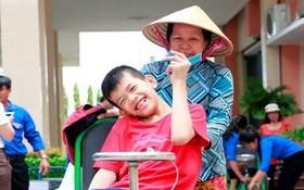隆安省一名落葉劑受害少兒在獲贈手搖輪椅後的喜悅。