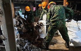 職能力量在清理曙光公司大火後的廢墟並噴灑消毒周圍環境。(圖源:VOV)