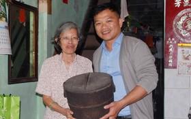 陳麗英老師(左)把放在家裡逾80年歷史的木製飯桶贈送給麒麟(右)。