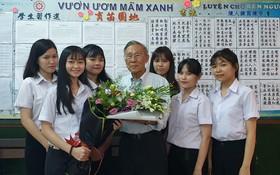 啟秀初中生向 55 年黨齡黨員、校長王沛川贈送鮮花。