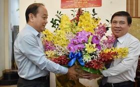 市人委會主席阮成鋒(右)向黎保霖老師贈送鮮花祝賀。(圖源:TL)