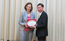 市人委會副主席陳永線(右)向奧地利聯邦經濟商會副秘書長瑪麗安娜‧庫納贈送紀念品。(圖源:VOH)