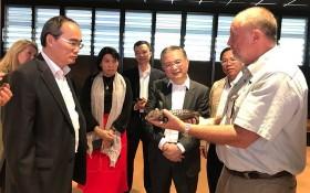 阮善仁同志(前左)參觀 Taronga 動物園,並聆聽該動物園專家介紹罕見鹹水鱷魚的特性。(圖源:喬峰)