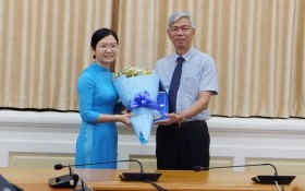 新任第六郡人委會副主席王清柳(左)從市人委會副主席武文歡手中接過人事委任《決定》和祝賀鮮花。
