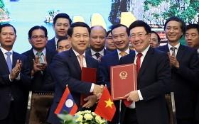 政府副總理、外交部長范平明(前右)與老撾外交部長沙倫塞‧貢瑪西簽署越南外交部與老撾外交部之間行動計劃。(圖源:外交部)