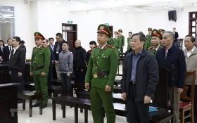 各被告人、法警及庭上所有出席者站立著聽取審判長宣讀判決書。(圖源:越通社)