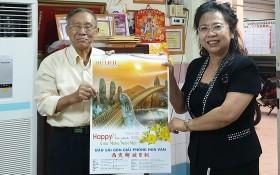 啟秀華文中心校長王沛川(左)向北京華文學院副院長劉香玲贈送本報的月曆作為紀念。