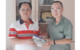 本市台商會會長鄭文忠(左)將歲暮濟貧款項交予本報編委兼編輯部主任范興代領。