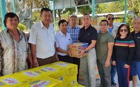 熱心人士劉根全(中右)代表眾友把食用品轉贈給該中心主任阮文石。