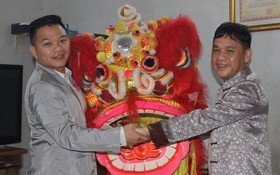 徐梓衡師傅(右)向筆者贈送一套醒獅。